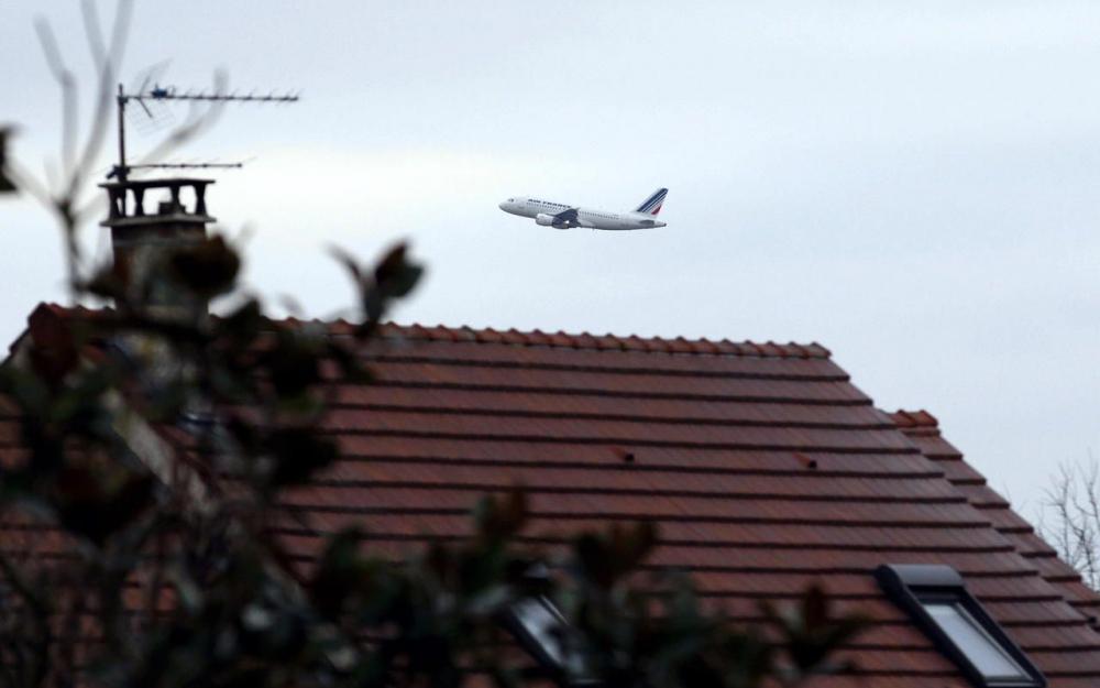 avion très bas audessus d'un toit d'habitation